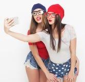 Deux amies d'adolescentes dans l'équipement de hippie font le selfie Images stock