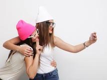 Deux amies d'adolescentes dans l'équipement de hippie font le selfie Photographie stock