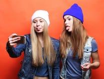 Deux amies d'adolescentes dans l'équipement de hippie font le selfie sur un pho Photographie stock libre de droits