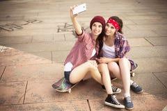 Deux amies d'adolescentes de brune dans le hippie équipent le shor de jeans Photo libre de droits