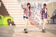 Deux amies d'adolescentes de brune dans le hippie équipent le shor de jeans Images libres de droits