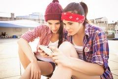 Deux amies d'adolescentes de brune dans le hippie équipent le shor de jeans Image stock