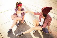 Deux amies d'adolescentes de brune dans le hippie équipent le shor de jeans Photos stock