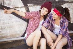 Deux amies d'adolescentes de brune dans le hippie équipent le shor de jeans Image libre de droits