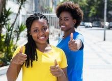 Deux amies d'afro-américain montrant le pouce  Image stock