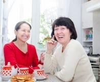 Deux amies d'une cinquantaine d'années buvant du thé Images stock