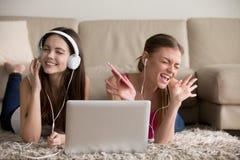 Deux amies dans des écouteurs ayant l'amusement à la maison Image stock