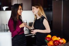 Deux amies dans des vêtements élégants détendant après vin d'achat, de boissons, riant et bavardant dans la cuisine Photos stock
