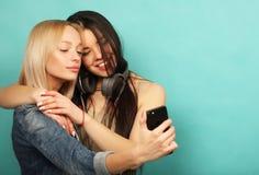 Deux amies dans l'équipement de hippie font le selfie à un téléphone Image stock