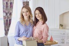 Deux amies dans leurs mains lors d'une réunion dans une chambre Photographie stock libre de droits