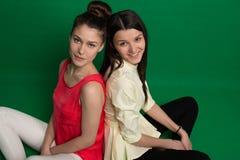 Deux amies de brune posant sur le fond vert Photo stock