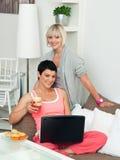 Deux amies de femme avec l'ordinateur portatif à la maison Photographie stock libre de droits