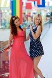 Deux amies de femme dans le centre commercial avec des cartes de crédit Photographie stock libre de droits