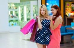 Deux amies de femme dans le centre commercial avec des sacs Image stock