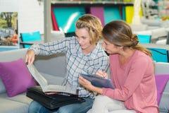 Deux amies de femme sur la brochure de lecture de sofa Image libre de droits