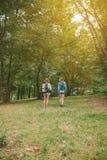 Deux amies de femmes avec des sacs à dos se tenant dans la forêt Image stock