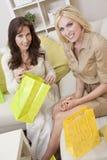 Deux amies de femmes avec des sacs à provisions autoguident à la maison Images libres de droits
