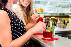 Deux amies de femmes en café barrent la longue boisson potable Photo stock
