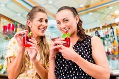 Deux amies de femmes en café barrent la longue boisson potable Images libres de droits