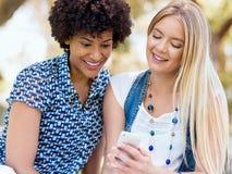 Deux amies de femmes en parc avec le téléphone portable Images libres de droits