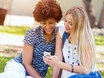 Deux amies de femmes en parc avec le téléphone portable Photos libres de droits