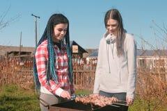 Deux amies de femmes font cuire la viande de shashlik sur le gril de charbon de bois sur l'arrière-cour Parler et sourire ensembl Photographie stock libre de droits