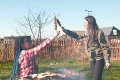 Deux amies de femmes font cuire la viande de shashlik sur le gril de charbon de bois sur l'arrière-cour Parler et sourire ensembl Image libre de droits