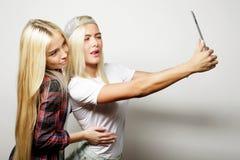 deux amies de hippie prenant le selfie avec le comprimé numérique, s Photos stock