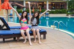 Deux amies de jeunes femmes apprécient avec des bras augmentés dans la piscine Images libres de droits
