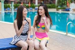 Deux amies de jeunes femmes apprécient dans la piscine Photographie stock libre de droits