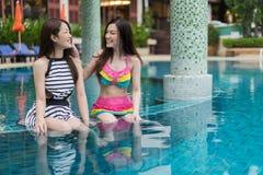 Deux amies de jeunes femmes apprécient dans la piscine Photo stock