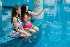 Deux amies de jeunes femmes apprécient dans la piscine Image stock