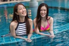 Deux amies de jeunes femmes apprécient dans la piscine Photo libre de droits