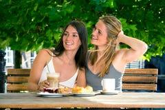 Deux amies de jeunes femmes en café de rue Photographie stock