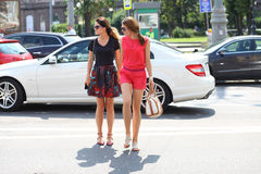 Deux amies de jeunes filles traversent la route Photo stock