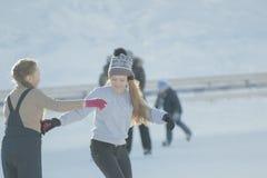 Deux amies de l'adolescence apprenant à patiner et ayant l'amusement à la piste Photos stock