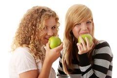 Deux amies de l'adolescence mangeant les pommes vertes Image stock