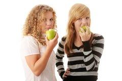 Deux amies de l'adolescence mangeant les pommes vertes Photos libres de droits