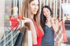 Deux amies de mode faisant des emplettes à Noël Photographie stock libre de droits