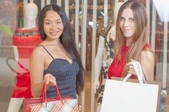 Deux amies de mode faisant des emplettes au mail Photo stock