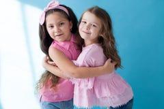 Deux amies de petites filles ensemble sur le fond bleu photo libre de droits
