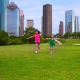 Deux amies de soeur courant tenant la main dans l'horizon urbain Photo stock