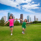 Deux amies de soeur courant tenant la main dans l'horizon urbain Images libres de droits