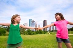 Deux amies de soeur jouant tenant la main dans l'horizon urbain Photographie stock