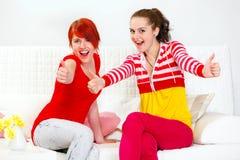 Deux amies de sourire affichant des pouces lèvent le geste Photo libre de droits