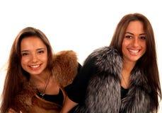Deux amies de sourire gaies dans des manteaux de fourrure Photo libre de droits