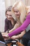 Deux amies de sourire positives de Caucaisan travaillant avec l'ordinateur portable Indosor Image libre de droits
