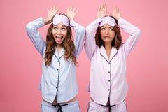Deux amies drôles de femmes dans des pyjamas d'isolement au-dessus du fond rose Photos stock