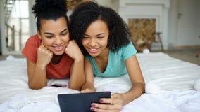 Deux amies drôles de métis gai partageant le media social utilisant la tablette et les entretiens se situant dans le lit à la mai Photographie stock libre de droits