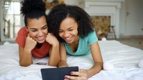 Deux amies drôles de métis gai partageant le media social utilisant la tablette et les entretiens se situant dans le lit à la mai Image stock